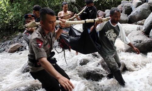 Cảnh sát Indonesia và dân làng di chuyển thi thể của một nạn nhân bị nước cuốn trôi. Ảnh: AFP