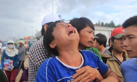 Trương Đình Huynh, con trai cả ông Trương Đình Bảy, ngư dân bị bắn ở Trường Sa, khóc ngất trời khi thấy thi thể của cha. Ảnh:  Lê Đình Dũng