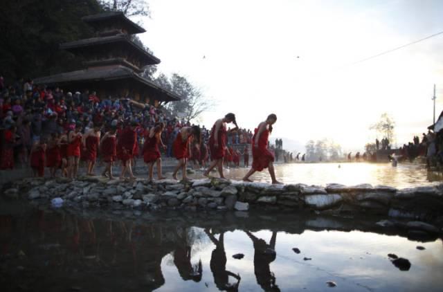 Tín đồ qua sông Triveni sau khi tắm dòng nước thánh trong lễ hội Bratakatha Swasthani ở  Panauti gần Kathmandu.