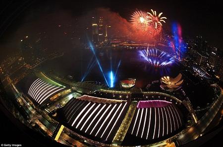 Pháo hoa thắp sáng bầu trời trên vịnh Marina, Singapore. Người dân viết lời ước của mình lên 25.000 hình cầu xếp dọc, vừa đón chào năm mới, vừa kỷ niệm 50 ngày Độc Lập. Ảnh: Reuters