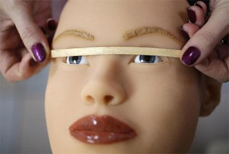 Nhân viên của Dreamdoll kiểm tra xem mắt của một búp bê tình dục này đã cân đối hay chưa.