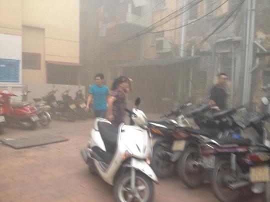Nhiều người dân mang xe máy ra sau tòa nhà bị cháy để tránh phát nổ