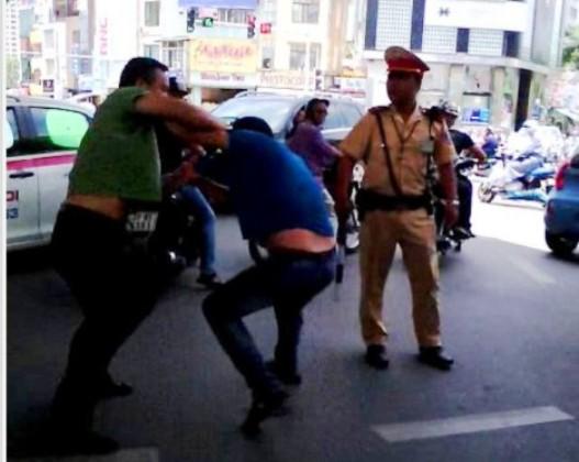 cảnh sát giao thông đứng nhìn người dân đánh nhau