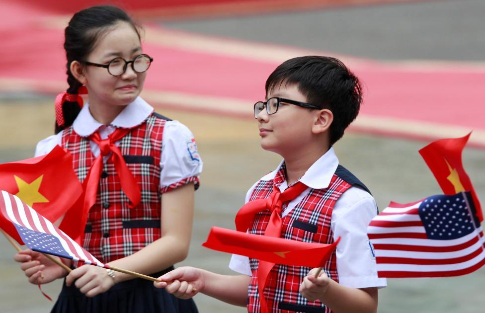 Học sinh tiểu học vẫy cờ Việt Nam – Mỹ chào đón chuyến thăm của Tổng thống Mỹ đến Hà Nội