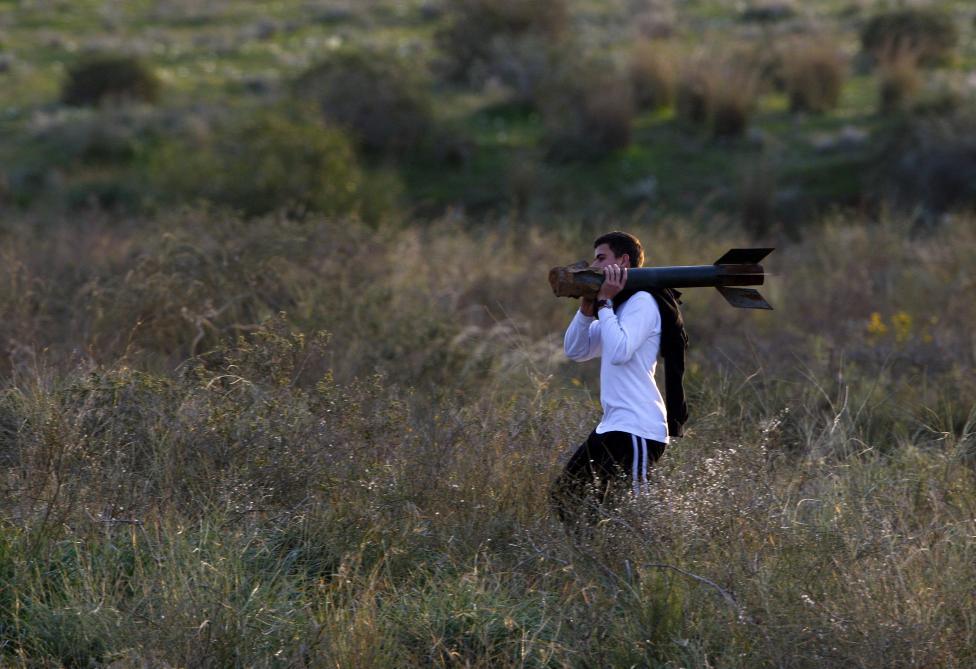 Một thanh niên người Israel đang vác trên vai xác quả tên lửa được phóng bởi lực lượng Palestine ở Gaza.