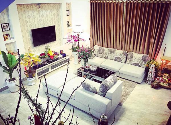 Phòng khách được bày biện ngăn nắp với bộ salon, tivi và dàn loa sang trọng
