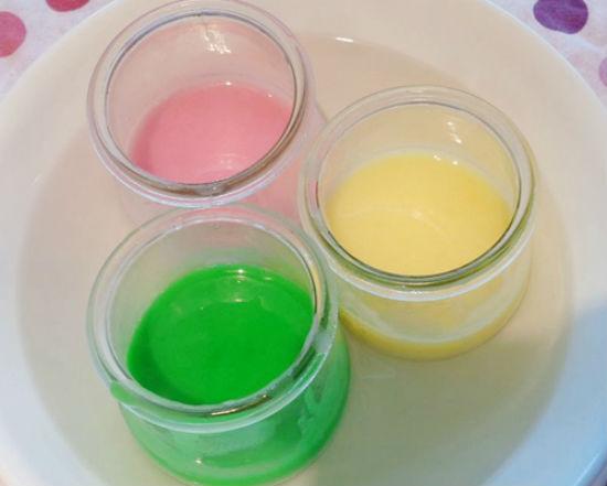 Chia thạch vào từng cốc nhỏ pha màu thực phẩm hoặc siro vào tạo màu cho thạch. Đặt các cốc thủy tinh này vào bát nước nóng để thạch không bị đông.