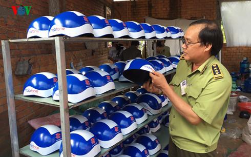 Lực lượng chức năng kiểm tra,thu giữ mũ bảo hiểm giả do anh Nguyễn Hoàng Phi làm chủ. Ảnh VOV