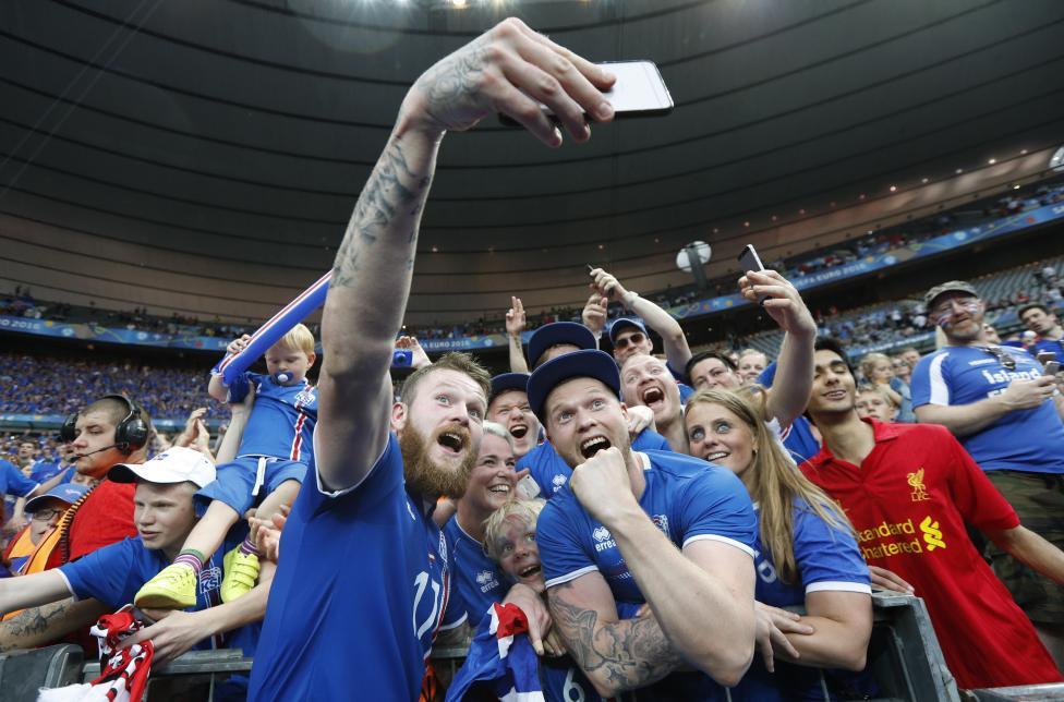 Aron Gunnarsson của đội Iceland đang ăn mừng chiến thắng cùng fan hâm mộ sau trận đấu với Áo.