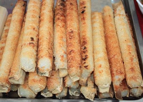 """Cơm lam được coi là món ăn đặc sản của núi rừng Tây Nguyên. Để làm được cơm lam ngon đòi hỏi một sự tỉ mỉ đến từng chi tiết. Đầu tiên phải chọn cây nứa ngô còn non, chặt lấy gióng lưng chừng nứa rồi phạt đi đầu mặt, dùng lá nút lại, chất củi xung quanh đốt cho sôi. Gạo nếp làm cơm lam phải chọn loại nếp trắng, dẻo, thơm, tốt nhất là """"khảu tan"""" (nếp tan). Ngâm gạo, vo sạch, rắc ít muối trộn đều rồi cho vào ống lam, cùng với dòng nước suối trong vắt sẽ tạo nên một cơm lam hương vị đặc biệt của núi rừng."""