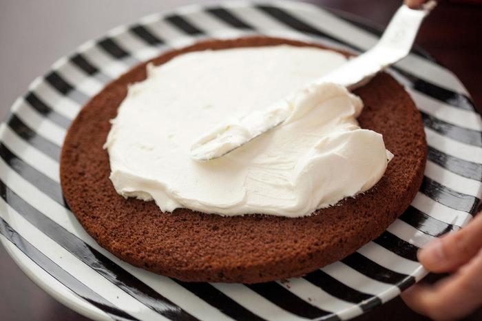 Phết một lớp kem mỏng vừa đánh lên phần bánh đã nướng.