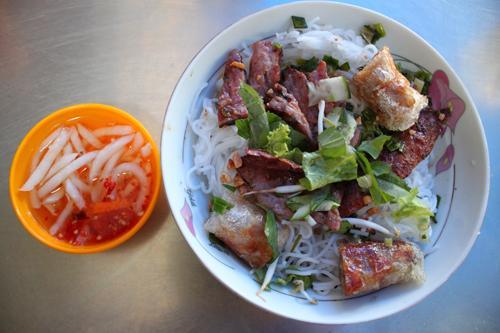 Lúc ăn, xếp rau xà lách đã thái nhỏ xuống dưới bát, bên trên để bún, thịt nướng, cà rốt và rắc ít đậu phộng lên bề mặt thịt. Chan nước mắm chua ngọt, trộn đều lên.