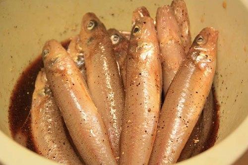 Rắc tiêu sọ và tiêu xay vào nồi cá rồi đổ hỗn hợp gia vị vào sao cho sâm sấp mặt cá, để 20 phút cho cá thấm gia vị.