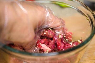 Tay đeo găng nilon sạch, trộn đều hỗn hợp thịt bò với các gia vị, ướp khoảng từ 15 đến 30 phút.