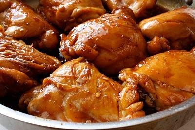 Tiếp theo, cho caramel, nước mắm, một ít muối, tiêu, và ớt bột vào, giảm nhỏ lửa và kho khoảng 20 phút cho thịt gà thật thấm. Sau đó, thêm hành gừng tỏi đã được phi thơm ở trên vào. Để sôi liu riu đến khi nước kho kẹo lại, thịt gà chín mềm thì tắt bếp.