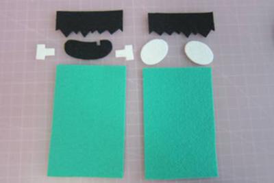 Cắt 2 tấm vải dạ xanh hình chữ nhật làm khuôn mặt, 2 tấm vải đen làm tóc và miệng, 2 tấm vải trắng hình oval làm đôi mắt và đôi tai.
