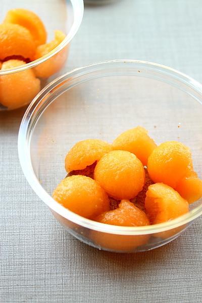 Dưa vàng để nguyên nửa quả, dùng thìa múc từng viên tròn, nhỏ và xếp lên trên chiếc bánh quy.