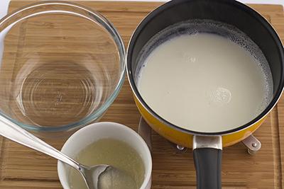 Đổ sữa nóng vào 1 bát sạch, cho tiếp hỗn hợp gelatin và nước vào bát sữa. Dùng máy đánh trứng đánh đến khi được hỗn hợp tan đều, đồng nhất.