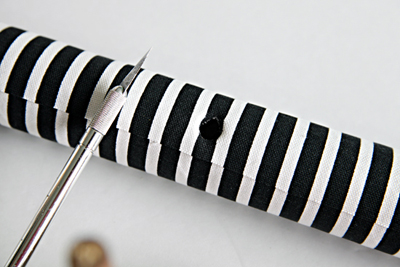 Khoét một lỗ tròn nhỏ giữa lõi giấy có đường kính bằng với đường kính thanh gỗ tròn.