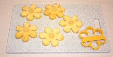 Dùng khuôn cắt hình bông hoa cắt từng miếng dứa tròn, tạo thành những bông hoa dứa 6 cánh.