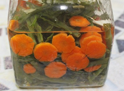 Tiếp theo xếp rau muống vào lọ thủy tinh đã tiệt trùng sạch, thêm cà rốt, ớt quả, tỏi, đổ hỗn hợp dấm đường đã nguội vào lọ thủy tinh, đậy kín. Để qua 1 ngày là có thể dùng được.