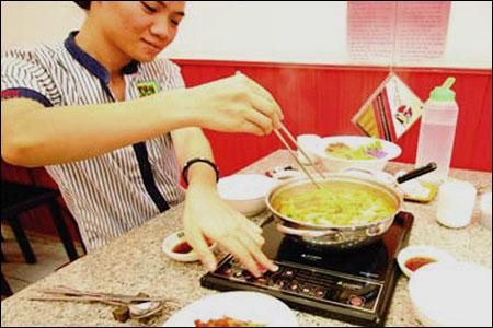 người sử dụng bếp điện để nấu lẩu