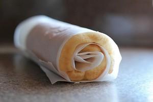 Từ từ đổ phần lòng trắng trứng vào hỗn hợp bột trên. Chuẩn bị khuôn, lót giấy nến rồi đổ bột bánh vào, đem nướng từ 8-10 phút thì đem ra. Khi bánh còn nóng, phủ thêm 1 tờ giấy nến nữa lên mặt bánh rồi cuộn lại, sau đó để nguội.