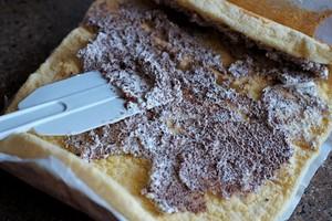 Bánh gato trải đều ra mặt phẳng, dùng dao hay thìa phết một nửa phần kem vừa đánh lên bề mặt rồi từ từ cuộn lại.