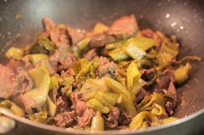 Khi thịt tái thì bỏ dưa chua vào, thêm chút hạt nêm và đảo đều để cho dưa ngấm gia vị và dầu ăn. Đổ thịt bò xào dưa ra đĩa.