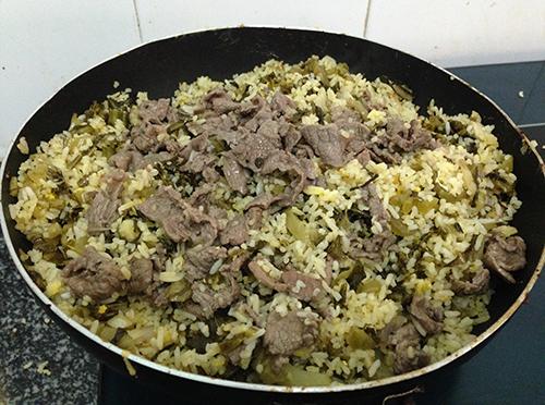 Khi cơm đã khô, trứng đã bám vàng từng hạt cơm rồi thì đổ đĩa thịt bò xào dưa vào đảo tiếp. Lưu ý là không được để cho nước xào dưa thịt bò rơi vào phần cơm rang.