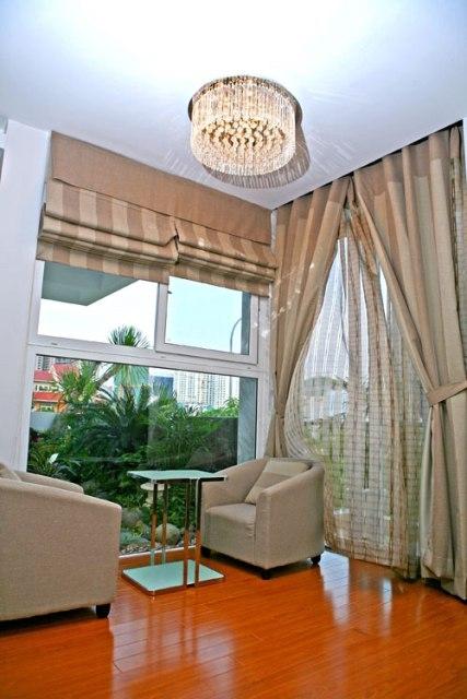 Một góc phòng ngủ với ghế sofa vuông dùng để cà phê sáng, nơi có thể nhìn ra ngoài khoảng lan can đầy hoa lá