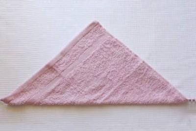 Rải khăn ra một mặt phẳng rồi gấp đôi khăn theo đường chéo.