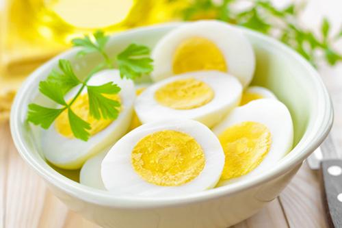 Luộc trứng chín, bóc vỏ và cắt đôi quả trứng theo chiều dọc