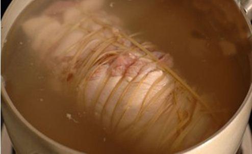 Thịt chân giò dùng lạt buộc thật chặt, cho vào nồi đun trên bếp lửa vừa