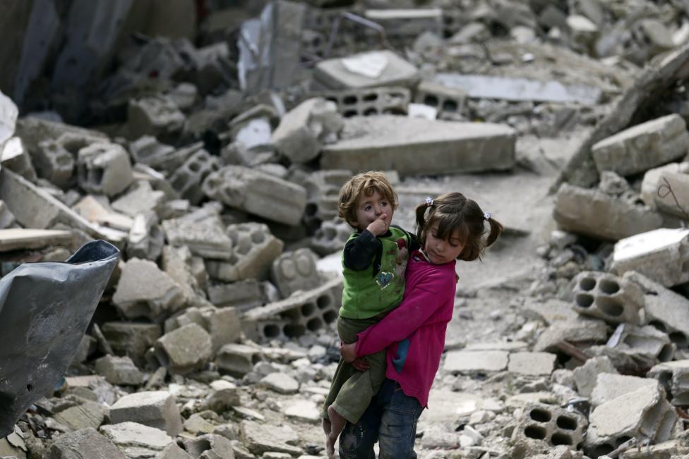 Cô bé Israa vừa bế em gái Boutol vừa cố gắng đi qua đống đổ nát còn lại  sau khi các tòa nhà tại khu phố Douma, Damascus bị sụp đổ do không kích. Ảnh: Reuters
