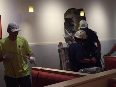 Đội cứu hộ phải đục xuyên tường để cứu chàng trai bị mắc kẹt giữa hai tòa nhà. Ảnh: CNN