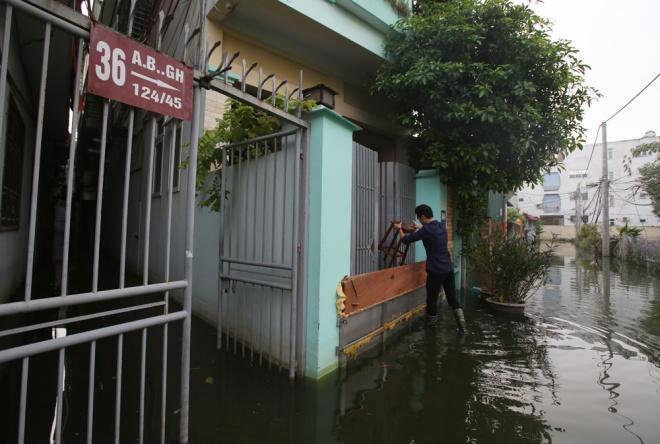 Hộ dân ở số nhà 38 ngách 124/45 bịt kín cửa ra vào. Chủ nhân cho biết, mưa lớn sau bão khiến hầm để xe của gia đình bị ngập dù đã dùng nhiều biện pháp ngăn chặn. Để vào nhà và tránh bị bẩn, các thành viên phải đi trên ghế gỗ. Ảnh:VnExpress