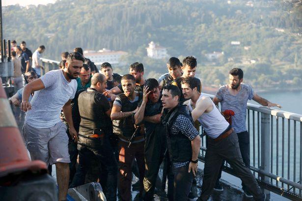 Cảnh sát cố gắng bảo vệ một người lính khỏi đám đông kích động sau khi lực lượng tham gia đảo chính đầu hàng trên cầu Bosphorus. Ảnh Reuters
