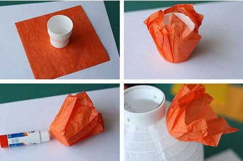 Cách làm: Đầu tiên, cắt giấy thành những hình vuông nhỏ đều nhau, đặt tờ giấy hình vuông vào nút chai để tạo hình cho giấy, dùng keo dán lên đèn lồng.