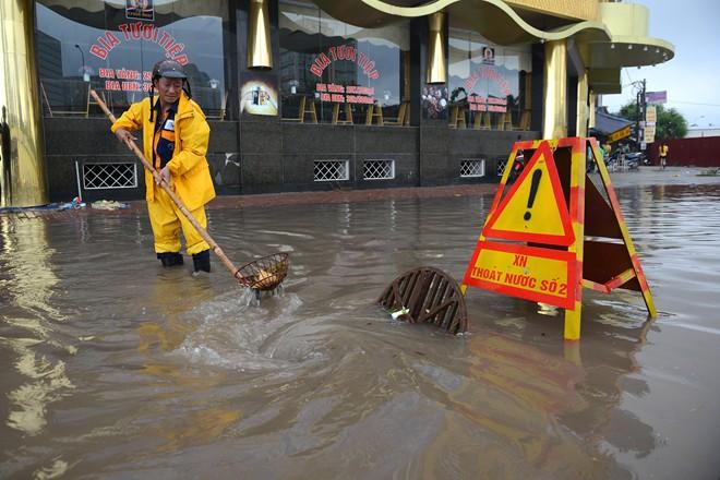 Công nhân xí nghiệp thoát nước số 2 có mặt tại các điểm ngập từ 6h30 trước cơn mưa lớn. 8h cơn mưa đã tạnh nhưng tới 10h nước vẫn chưa rút. Có những điểm ngập sâu quá đầu gối.