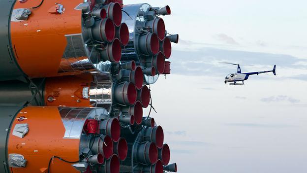 Một máy bay trực thăng của cảnh sát bay qua tàu vũ trụ Soyuz TMA-14M. Đây là chiến tàu được vận chuyển đến bệ phóng tại Baikonur Cosmodrome. (Shamil Zhumatov / Reuters)