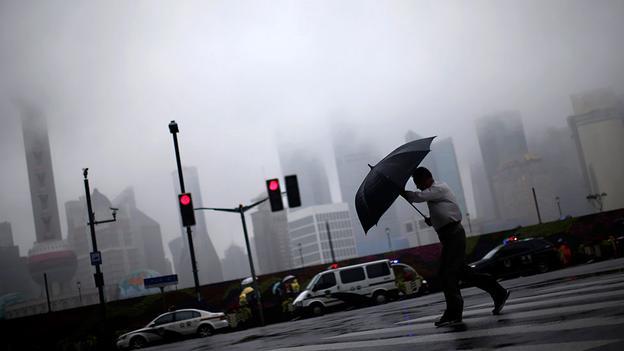 Một người đàn ông trung niên đang cố gắng để giữ được chiếc ô của mình chống lại những đợt gió và mưa tầm tã do ảnh hưởng của cơn bão Fung-Wong đi gần khu vực ven biển của Thượng Hải. (Carlos Barria / Reuters)