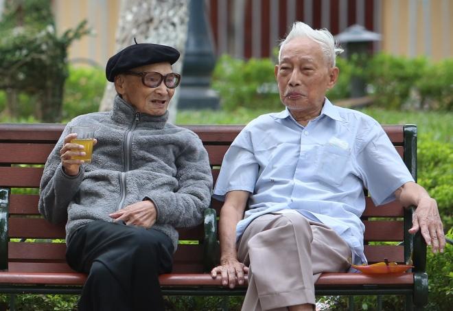 Hai cụ già vui vẻ trò chuyện cùng nhau trong công viên nhân một ngày Hà Nội se lạnh. Ảnh: Vnexpress