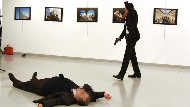 Đại sứ Nga Andrei Karlov ngã xuống sàn nhà sau khi bị Mevlut Mert Altintas bắn. Ảnh: Reuters