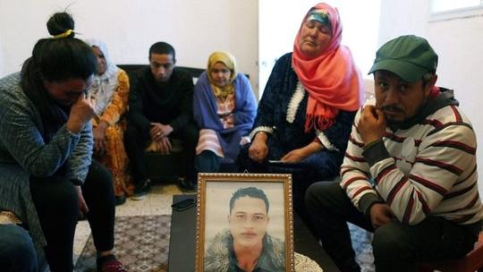Khủng bố IS: Gia đình nghi phạm vụ khủng bố ở Đức bên ngồi quanh bức chân dung của hắn tại Tunisia. Ảnh: EPA