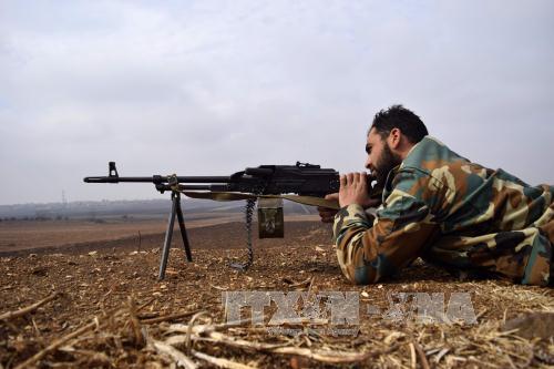 Chiến sự Syria: Lực lượng đối lập Syria giao tranh với quân đôi Chính phủ Syria tại làng Teir Maalah, tỉnh Homs ngày 5/12. Ảnh: AFP/TTXVN