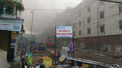 Sáng nay, ngọn lửa cơ bản được khống chế nhưng khói vẫn đen ngòm. Ảnh: pháp luật TP. Hồ Chí Minh