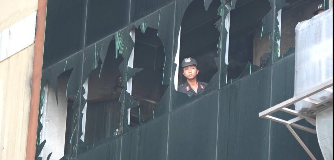Cảnh sát cơ động vào bên trong hiện trường vụ cháy đưa hàng hóa ra ngoài. Ảnh: Tuổi trẻ