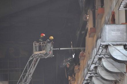 Hiện tại, lực lượng chữa cháy vẫn đang phun nước bên trong tòa nhà. Ảnh: Tiền Phong