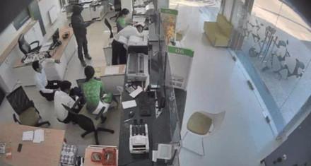 Tên cướp dùng súng khống chế nhân viên ngân hàng Vietcombank. Ảnh cắt từ camera ngân hàng